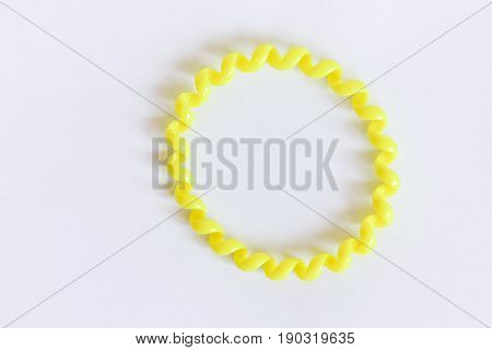Yellow plastic hair elastic on a white background. Hair clip. Used for making different hairstyles.