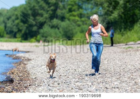Mature Woman Jogs With A Dog Riverside