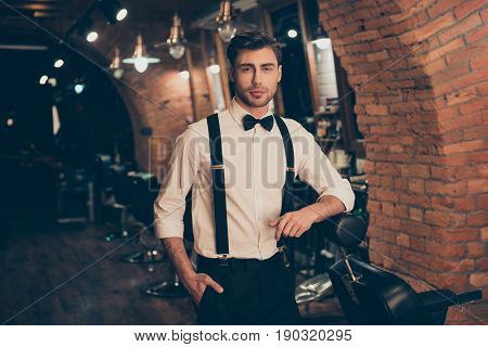 Welcome to barber shop! Handsome classy dressed brunette guy with bristle is standing near the chair. Looking confident and professional