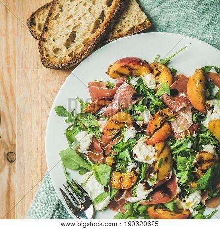 Arugula, prosciutto, mozzarella and grilled peach salad in white plate over blue napkin and wooden board, top view, square crop
