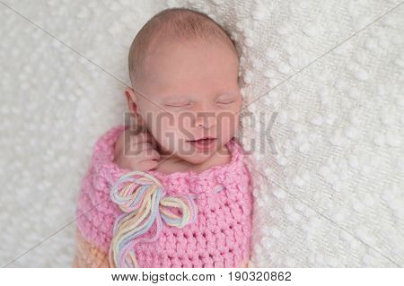 Headshot of a smiling three week old newborn baby girl bundled up in a light pink crocheted snuggle sack. She is lying on a white bouncle blanket.