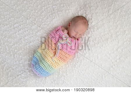 A three week old newborn baby girl bundled up in a rainbow colored snuggle sack. She is lying on a white bouncle blanket.