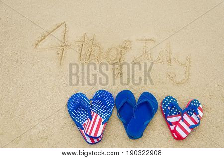 Independence USA background with flip flops on the sandy beach near ocean