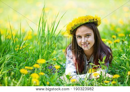 Cute young girl wearing wreath of dandelions and smiling while lying on grass in park