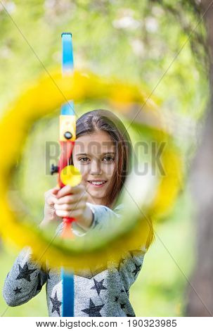 Young girl archer with bow aiming through flower wreath and smiling