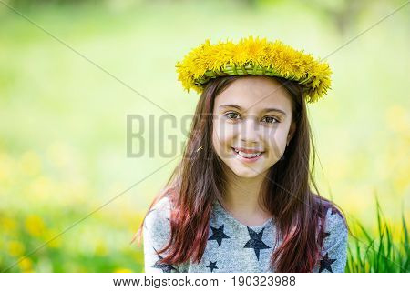 Cute young girl wearing wreath of dandelions and smiling outdoors