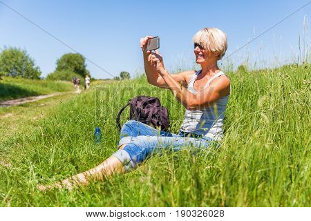 Mature Woman Makes Selfie Photos With A Phone