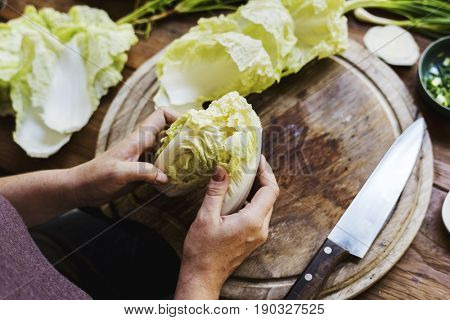 Hands chopping chinese cabbage on a wooden cutting board