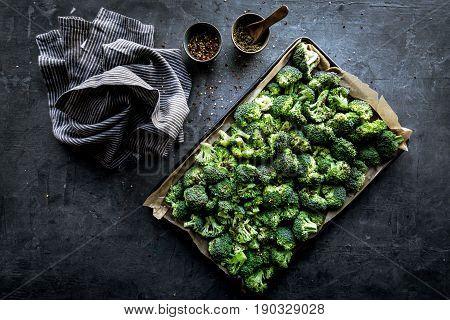 Fresh raw broccoli prepared for roasting on a flat pan