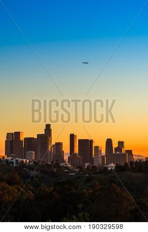 A commercial airliner flying over downtown Los Angeles at Dusk
