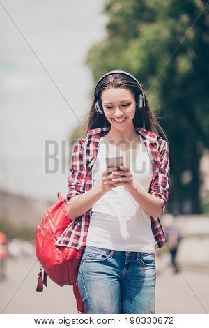 Carefree Girl Is Listening To Favourite Song Outside, Walking On The Spring Street, Wearing Cozy Out