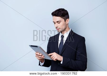 Focused Handsome Young Brunete Stock-market Broker Is Typing On His Tablet, Standing In A Formal Wea