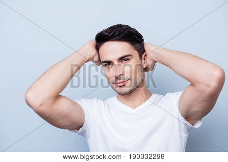 Confident Smiling Handsome Young Man In White T Shirt. Standing On The Pure Background, Fixing His P