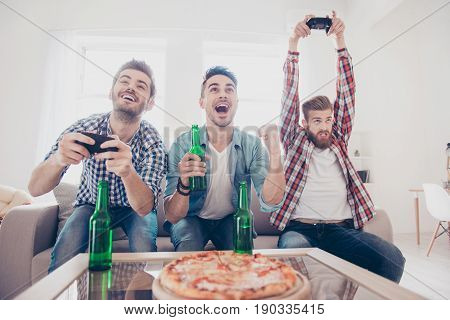 Crazy, Fun, Joy, Winners And Looser! Young Men Are Sitting On Couch And Playing Video Games Indoors
