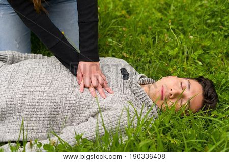 Beautiful woman giving first aid to a handsome young man, cardiopulmonary resuscitation, in a grass background.