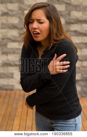 Young beautiful woman feeling bad and touching her arm, cardiopulmonary resuscitation concept, in a blurred background.