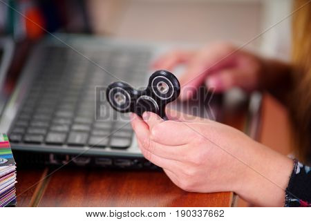 Young woman holding a popular fidget spinner toy in her hand while she is working in her computer on office background.
