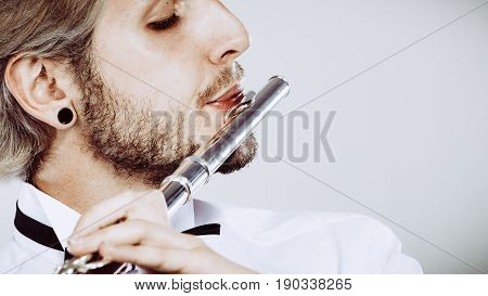 Flute music playing professional male flutist musician performer. Young elegant stylish man with instrument close up
