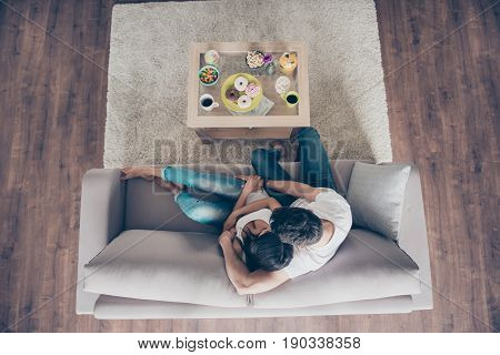 Top View Of A Married Couple In The Morning. They Are Hugging On The Beige Sofa Indoors At Home, Wea