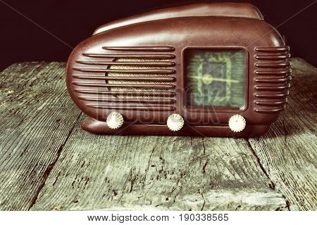 Vintage photo of old radio standing on the old wooden desk. Released in 1953. Black background. All potential trademarks are removed and blurred.
