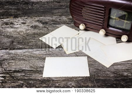 Vintage photo of old radio standing on the old wooden desk. Blank old photos are placed in front of the radio. Suitable for your text. All potential trademarks are removed and blurred.