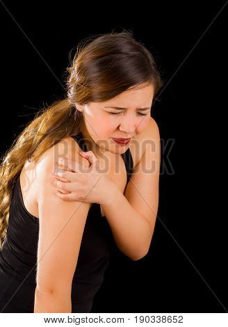 Beautiful young woman suffer from shoulder pain in a black background.