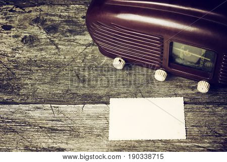 Vintage photo of old radio standing on the old wooden desk. Blank old photo is lying in front of the radio. Suitable for your text. All potential trademarks are removed and blurred.