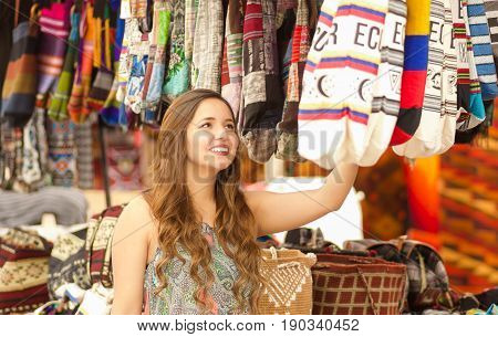 Beautiful woman holding an andean traditional handbag clothing textile yarn and woven by hand in wool, colorful fabrics background.