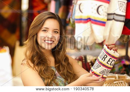 Close up of a beautiful woman holding an andean traditional handbag clothing textile yarn and woven by hand in wool, colorful fabrics background.