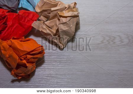 Colorful paper on white wooden background .