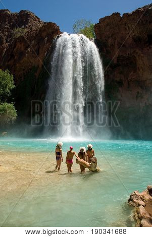 Beautiful group of women standing in front of the world famous Havasu Falls in Arizona