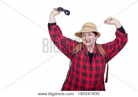 Funny older woman with backpack poses on white background. Tireless woman wears red plaid shirt and yellow straw hat. Her right hand holds sunglasses. Elderly people traveling concept