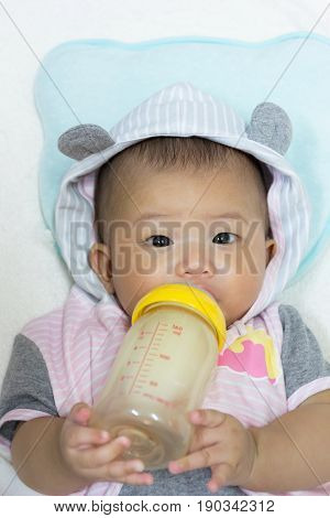Close Up Asian cute new born baby feeding milk mother in bottle.