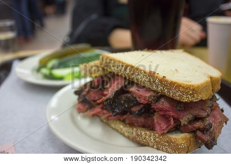 A delicious pastrami sandwich with side of pickles