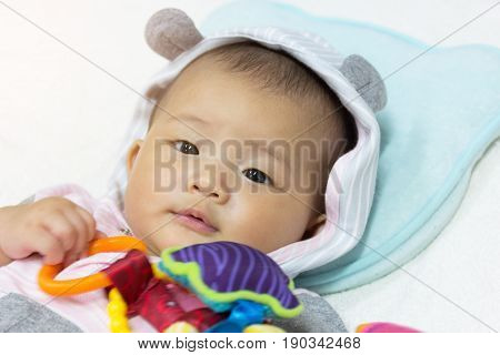 Close Up Asian cute new born baby playing toys on white bed.