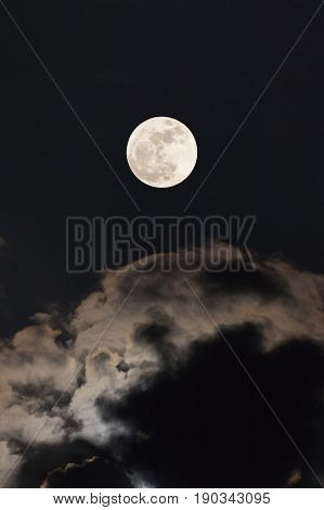 The Moon at it largest also called supermoon with night sky and clouds.