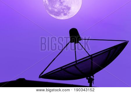 Satellite dish for communication broadcast on the roof with supermoon sky background twilight time silhouette purple background effect light with copy space.