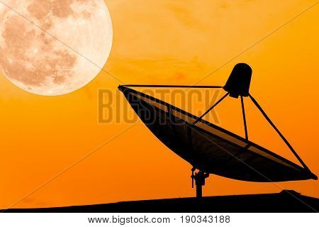 Communication satellite dish on the roof with supermoon sky background twilight time silhouette orange background effect light with copy space.