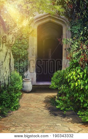 Cute footpath leads to ancient arched entrance surrounded by lush foliage. Sunrise light floods upper left corner. Vertical shot