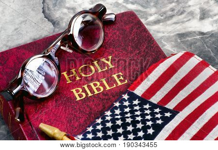 American flag bible and eyeglasses on marble table..