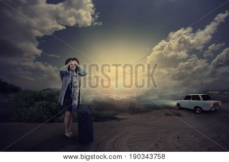 Scared mature woman with black suitcase holds head with hands. She standing in dark desert road. Panicing woman does not know what to do. It seems she was dropped from white car driving away. Dramatic clouds in the dark sky