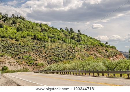 Bright green colors of spring contrast with a bit of red rock on this mountain road