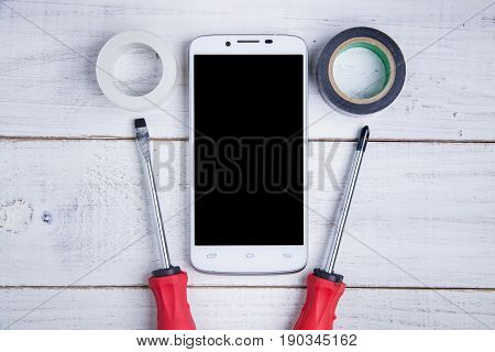 Smartphone And Equipment Repair On The White Wooden Background.