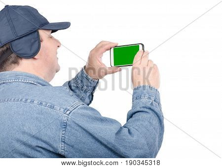 Fat chubby faced man looks at chroma key screen on cellphone on white background. Traveling fifty years old man takes pictures. He wearing denim shirt and navy cap with ear flaps. Elderly tourism concept