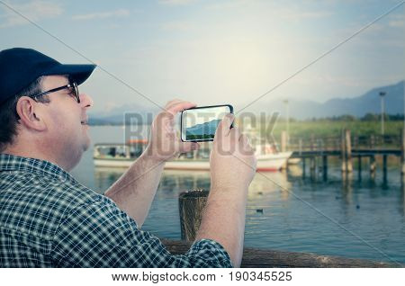 Older man takes mountains pictures with mobile phone from highland lake pier. Fat man with chubby face wears plaid shirt and navy cap. Aged people traveling concept