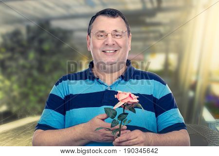 Smiling chubby faced mature man holds a rose in his hand and looking at the camera. Horizontal medium close-up shot on blurred outdoors cafe background