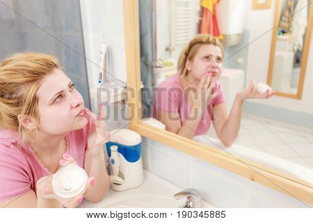 Woman Applying Face Cream With Her Finger