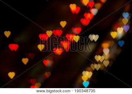 Bokeh of hearth shape of light from building or traffic road for valentine background.