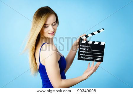 Woman holding professional film slate movie clapper board. Hollywood production objects concept. Studio shot on blue background.