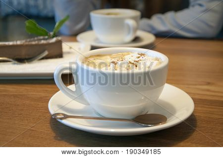 White cup of coffee in a Viennese close-up at a cafe.